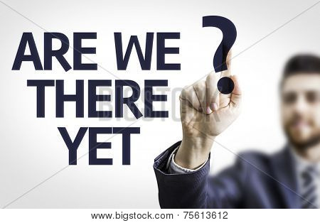 Business man pointing to transparent board with text: Are We There Yet?
