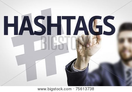 Business man pointing to transparent board with text: Hashtags
