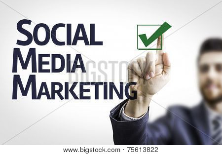 Business man pointing to transparent board with text: Social, Media, Marketing