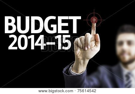 Business man pointing to black board with text: Budget 2014-15
