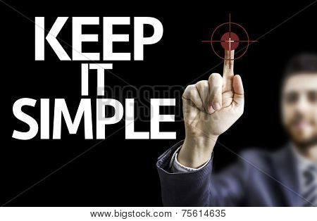Business man pointing to black board with text: Keep It Simple