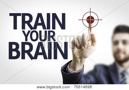 Business man pointing to transparent board with text: Train your Brain