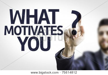 Business man pointing to transparent board with text: What Motivates You?