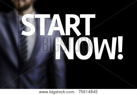 Start Now written on a board with a business man on background