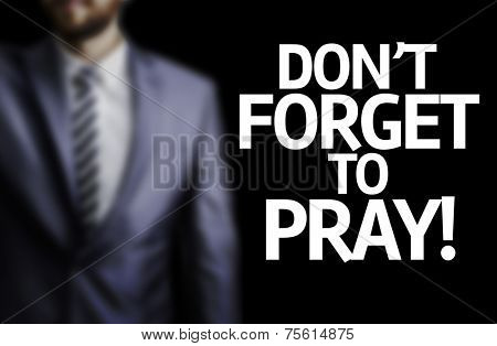 Don't Forget to Pray written on a board with a business man on background