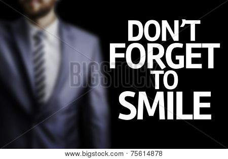 Don't Forget to Smile written on a board with a business man on background