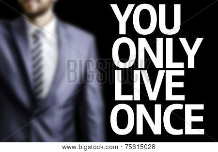 You Only Live Once written on a board with a business man on background