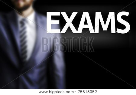 Exams written on a board with a business man on background