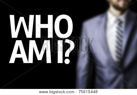 Who Am I? written on a board with a business man on background