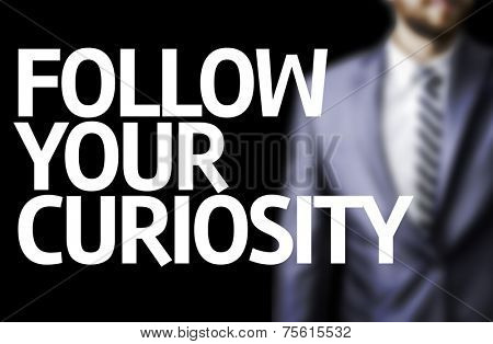 Follow your Curiosity written on a board with a business man on background