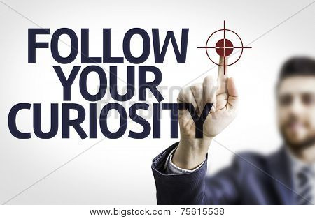 Business man pointing to transparent board with text: Follow your Curiosity