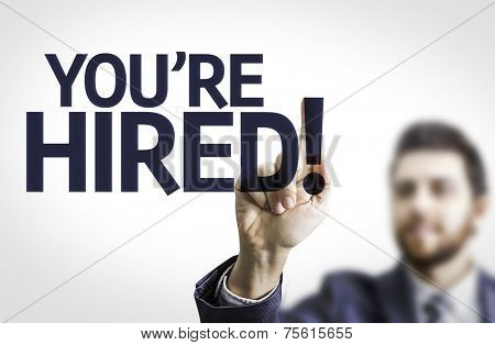 Business man pointing to transparent board with text: You're Hired!