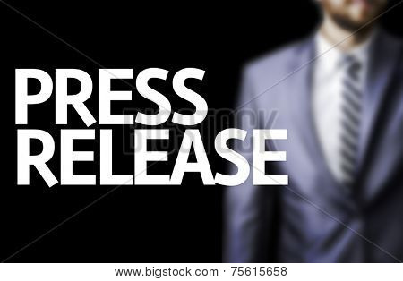 Press Release written on a board with a business man on background