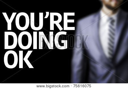 You Are Doing Okay written on a board with a business man on background