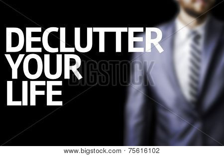 Declutter Your Life written on a board with a business man on background
