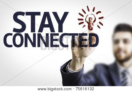 Business man pointing to transparent board with text: Stay Connected