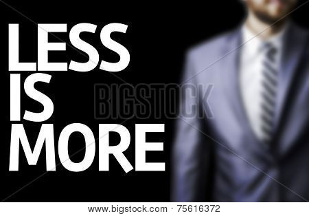 Less is More written on a board with a business man on background