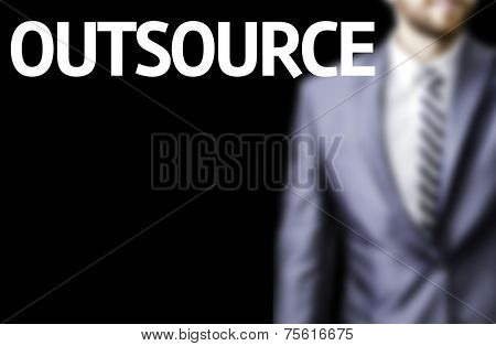 Outsource written on a board with a business man on background