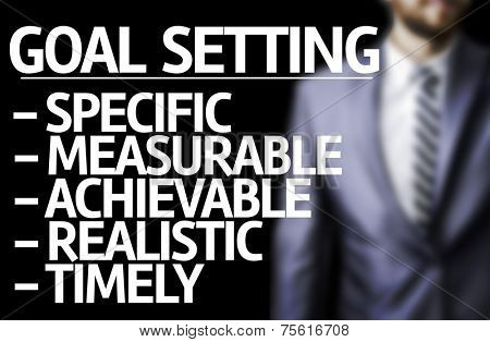Description of Goal Setting written on a board with a business man on background