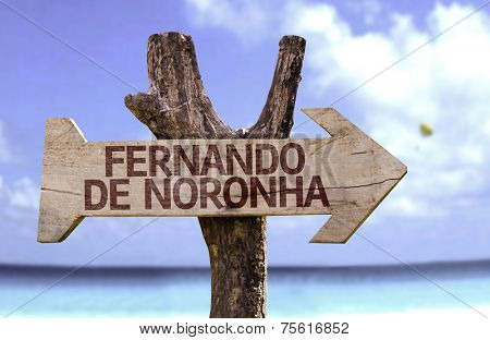 Fernando de Noronha wooden sign with a beach on background