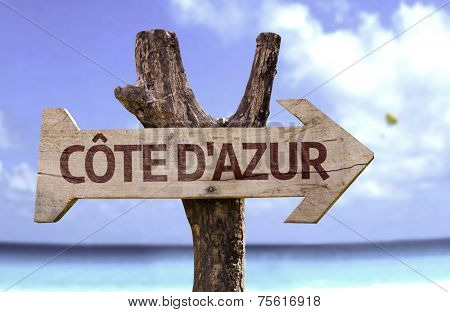 Cote Dazur wooden sign with a beach on background