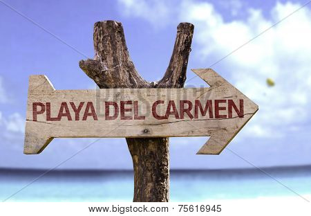 Playa del Carmen wooden sign with a beach on background