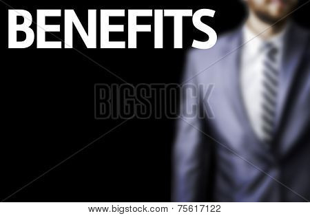 Benefits written on a board with a business man on background