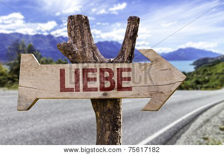 Love (In German) wooden sign with a road background
