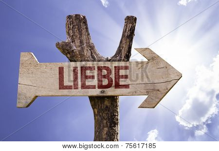 Love (In German) wooden sign on a beautiful day