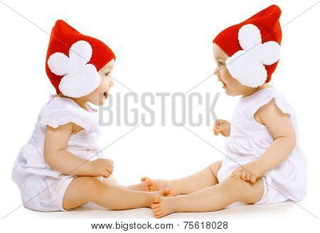 Two Funny Baby Twins In Hats Sitting Face To Face