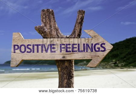 Positive Feelings wooden sign with a beach on background