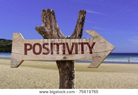Positivity wooden sign with a beach on background