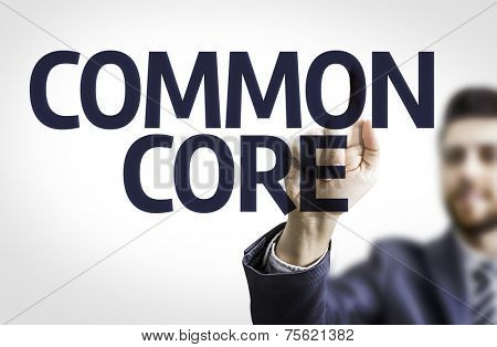 Business man pointing to transparent board with text: Common Core