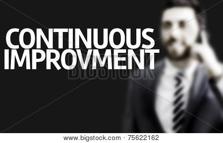 Business man with the text Continuos Improvement in a concept image
