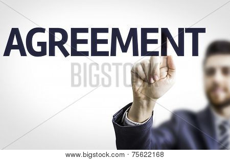 Business man pointing to transparent board with text: Agreement