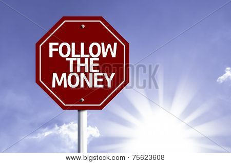 Follow the Money written on red road sign with sky background