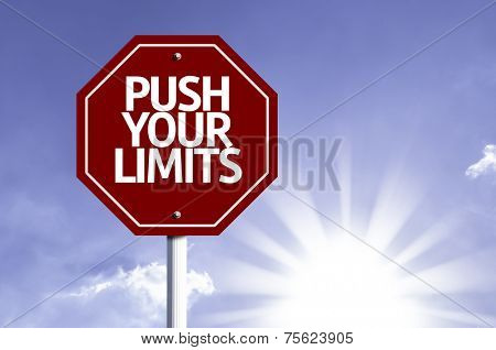 Push your Limits written on red road sign with a sky on background