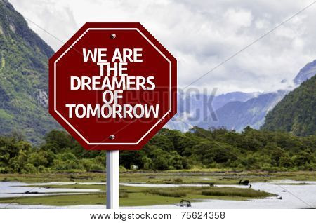 We Are The Dreamers Of Tomorrow written on red road sign with landscape background
