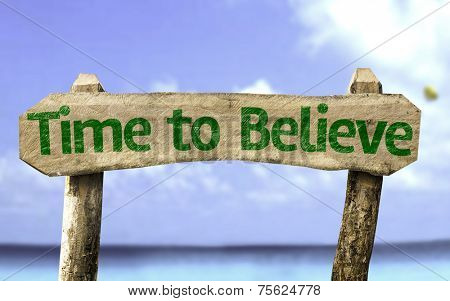 Time to Believe wooden sign with a beach on background