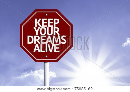 Keep Your Dreams Alive written on red road sign with a sky background