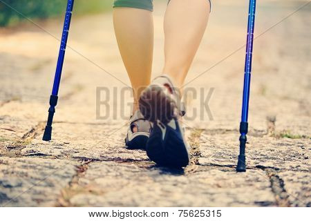 young fitness woman legs walking on forest trail