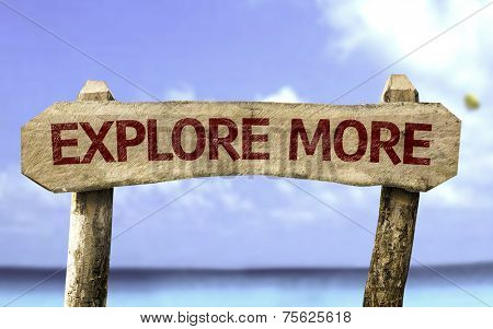 Explore More wooden sign with a beach on background