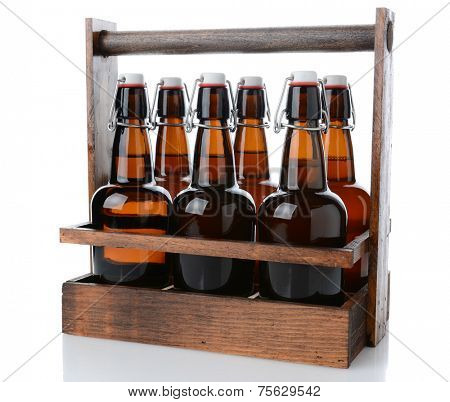 Closeup of an antique wooden six pack beer carrier with swing top beer bottles on a white background with reflection.
