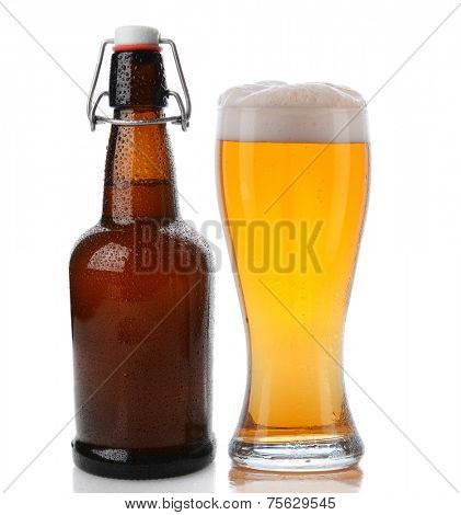 Closeup of a glass of beer with a frothy head next to a swing top brown beer bottle. Straight on shot on a white background with reflection. Both items are cover with water drops.