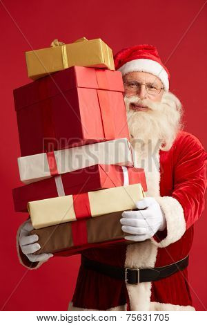 Generous Santa with pile of giftboxes looking at camera