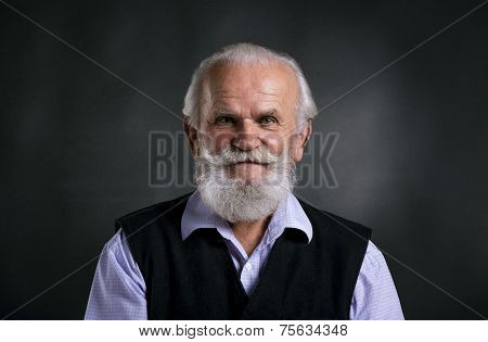 Old bearded man on black background