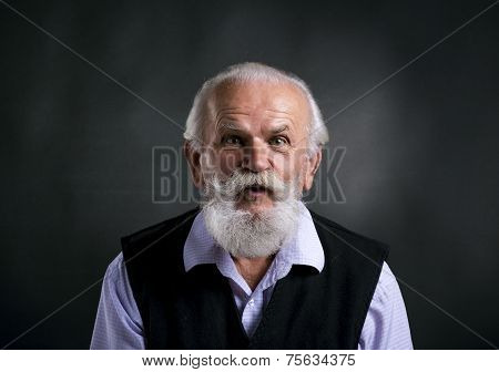 Old surprised bearded man on black background