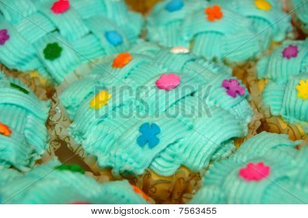 cupcake with green coating and sugar candies