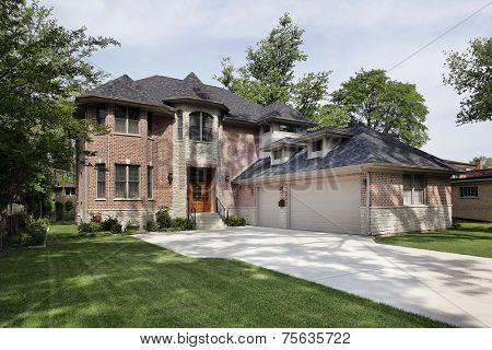 Brick suburban home with three car garage