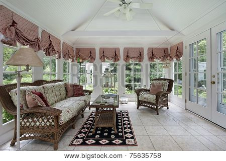 Sun room in modern home with wicker furniture